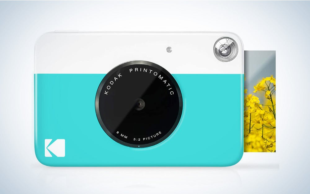 One of the best Kodak instant camera models, a white and teal model, printing a photo out of its side.