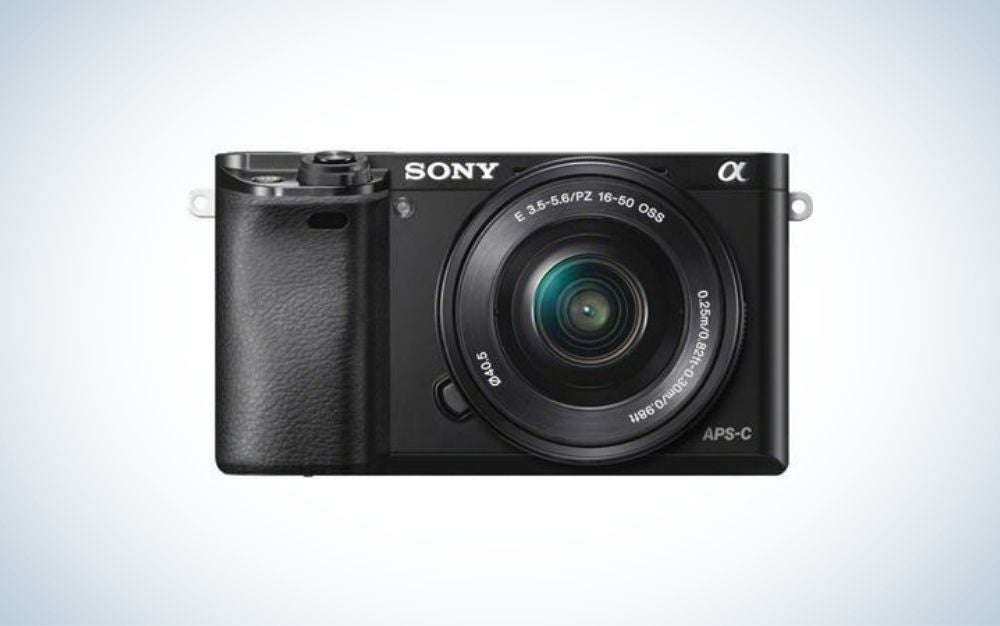 A small black camera with lens attached, which is the best camera for beginners on a budget.