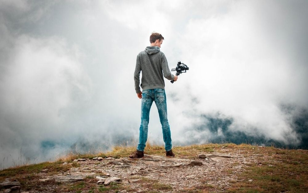 A boy in jeans standing on a rock with a professional camera in his hand filming clouds in front of him.