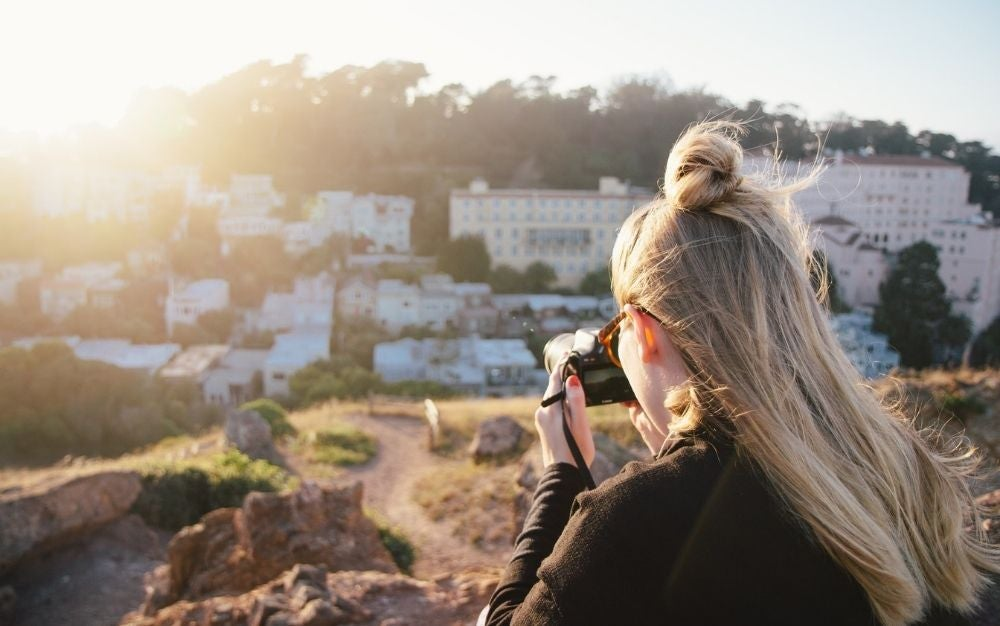 A blonde woman with a black camera in her hands taking pictures in front of the sun and some white houses.