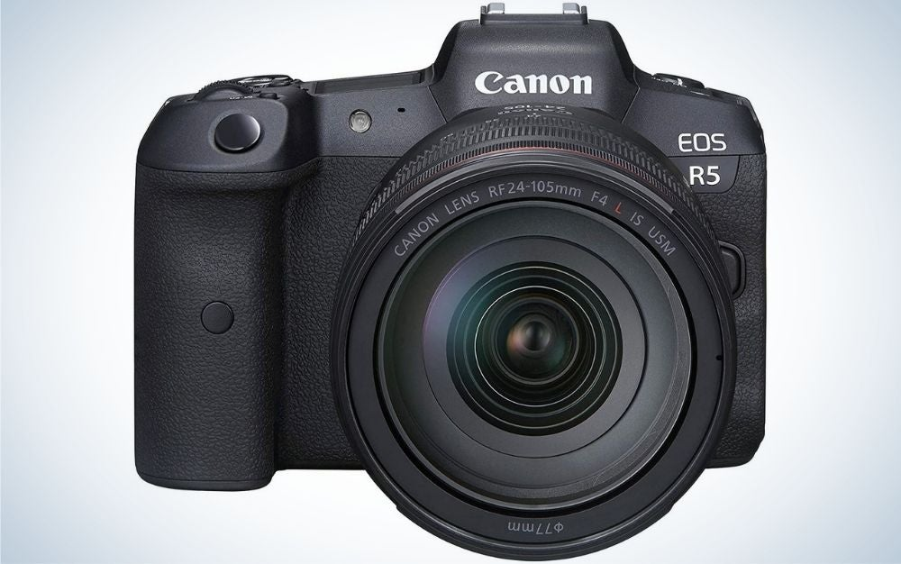A professional camera with black color and with black lens in front of it.