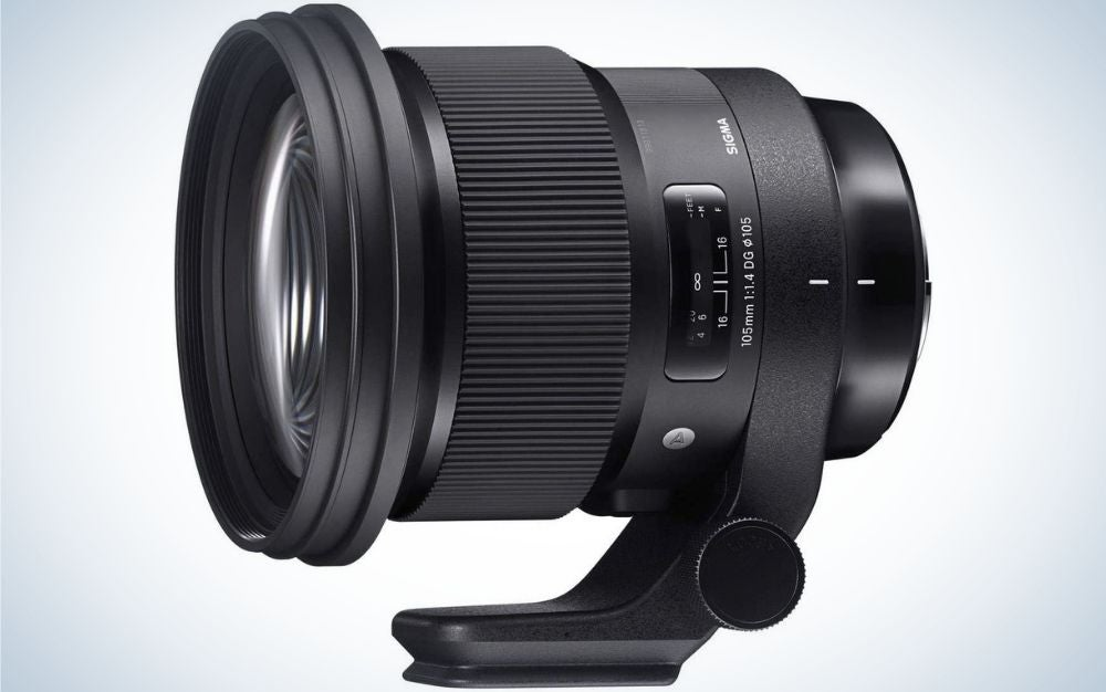 An all-black lens of a professional camera which looks sideways and with a light-colored glass front lens with a support to stand on.