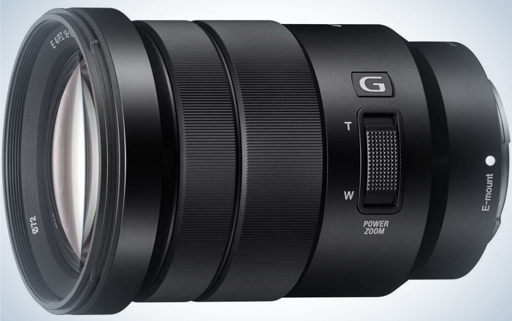 An all-black lens of a professional camera which looks sideways and with a light-colored glass front lens.