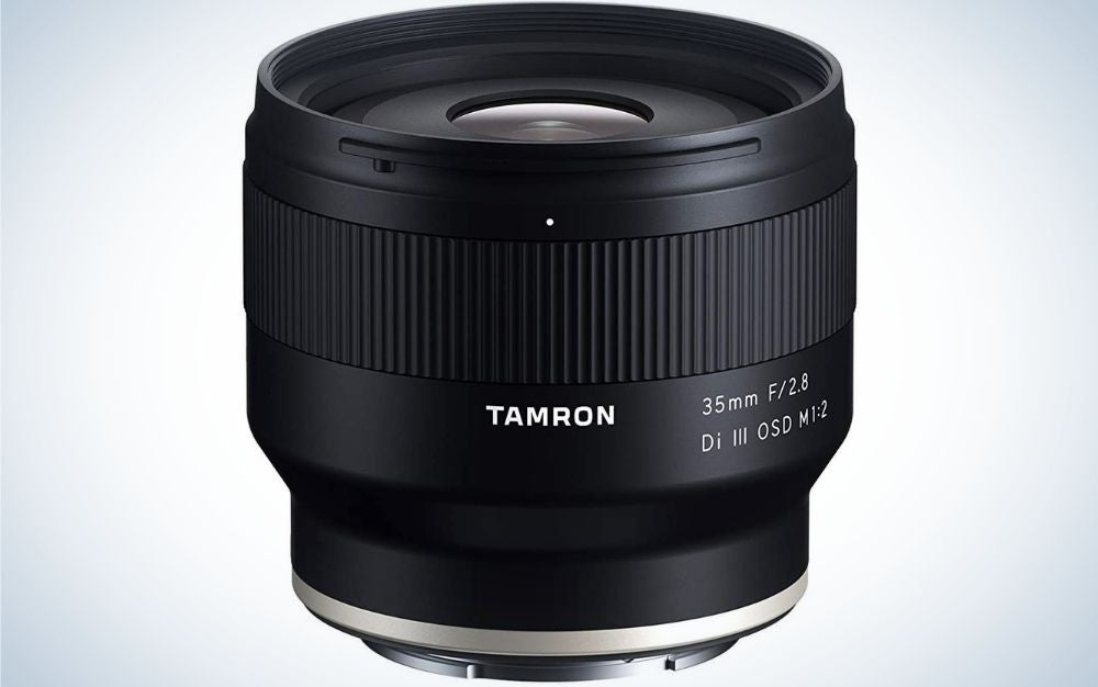 An all-black lens of a professional camera which stands on its feet with a lens from above and a lens in front of light glass and silver at the bottom.