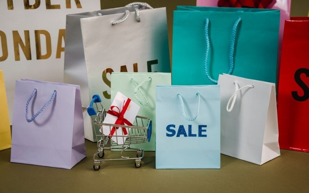 A lots of paper bags with with and light blue color with sale written into them.