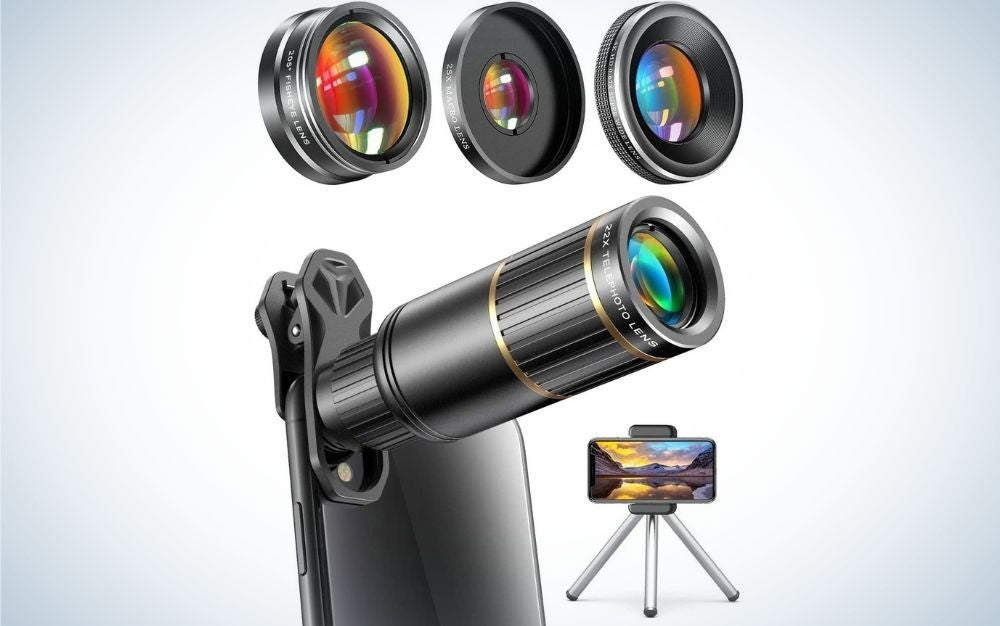 A black smartphone holder with three legs and a smartphone in it as well as some small circular lenses in neon color.