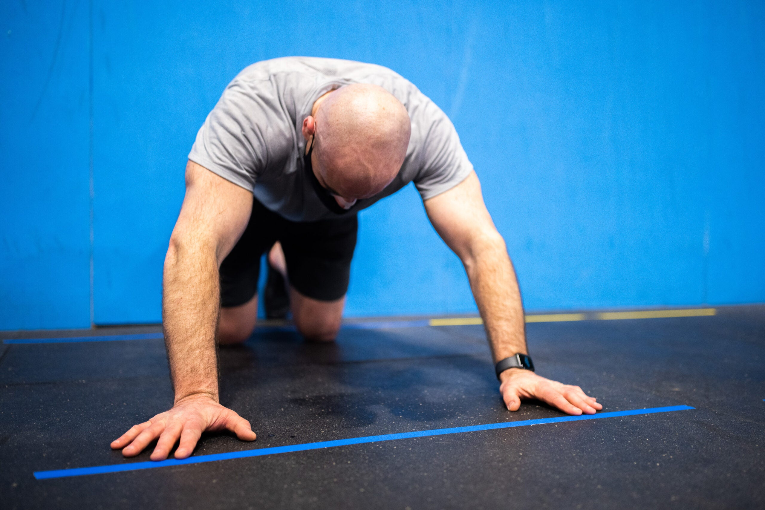A man on hands and knees on an exercise mat, doing push ups