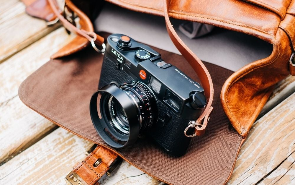 A professional black camera with some orange leather straps placed on the pocket of a brown bag.