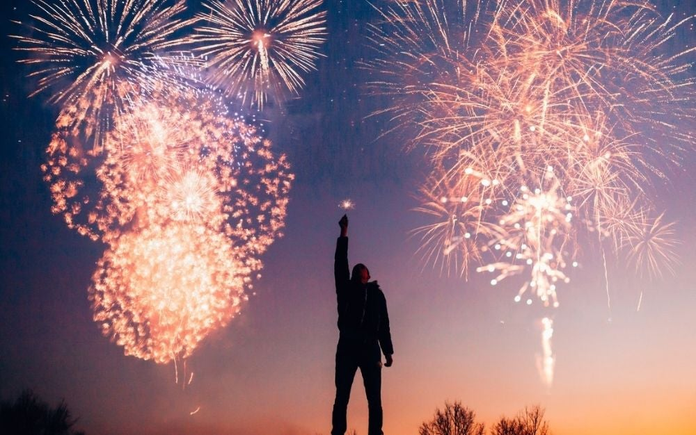 A man raising his hand and watching the fireworks shining in the sky.
