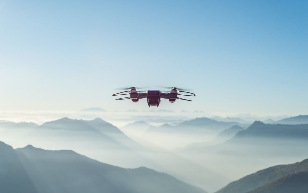 A black drone with four propellers at a height at the top of the mountains with a few clouds from behind.
