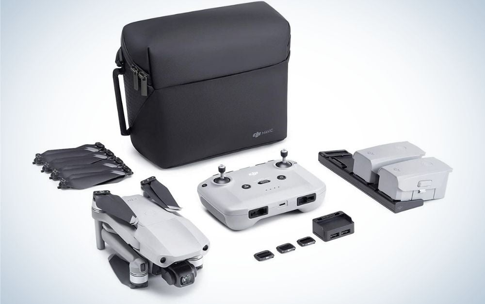 A black square bag as well as some accessories which are part of the shaping of a white drone with and complementary black parts.