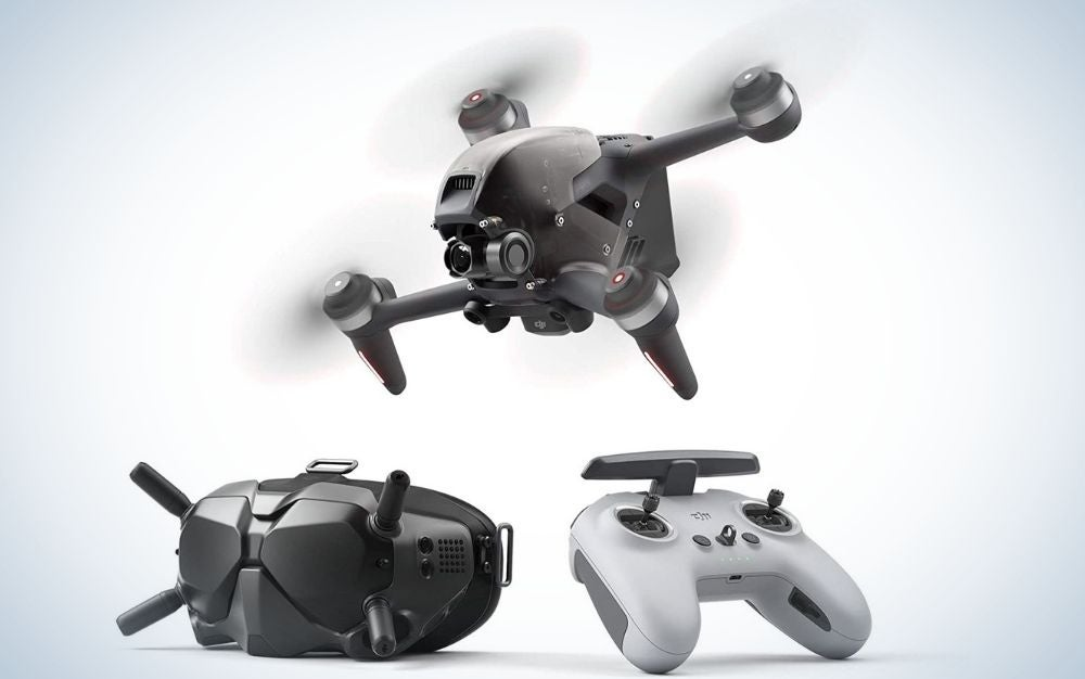 A black drone and a gray remote control as well as another machine with two black antennas as well.