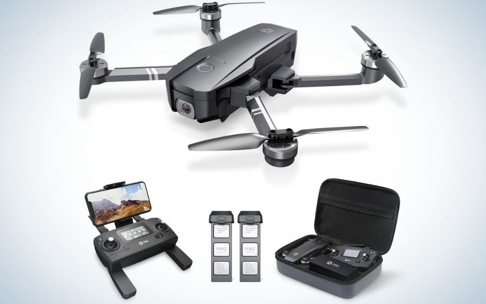 A black drone all with four propellers, with a black square box with some remote controls inside, with a camera mounted on a black device as well as two black strips complementing the drone set.