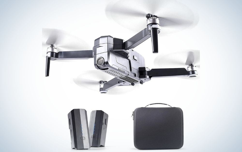 A white drone with four moving propellers as well as a square black bag, and two long rectangular silver boxes.
