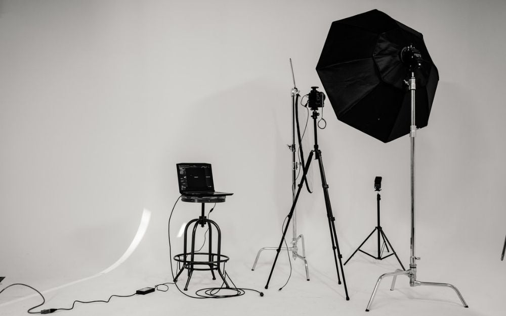 A photo studio which has some light black and white umbrellas as well as some bags and sets that help in the photography process.