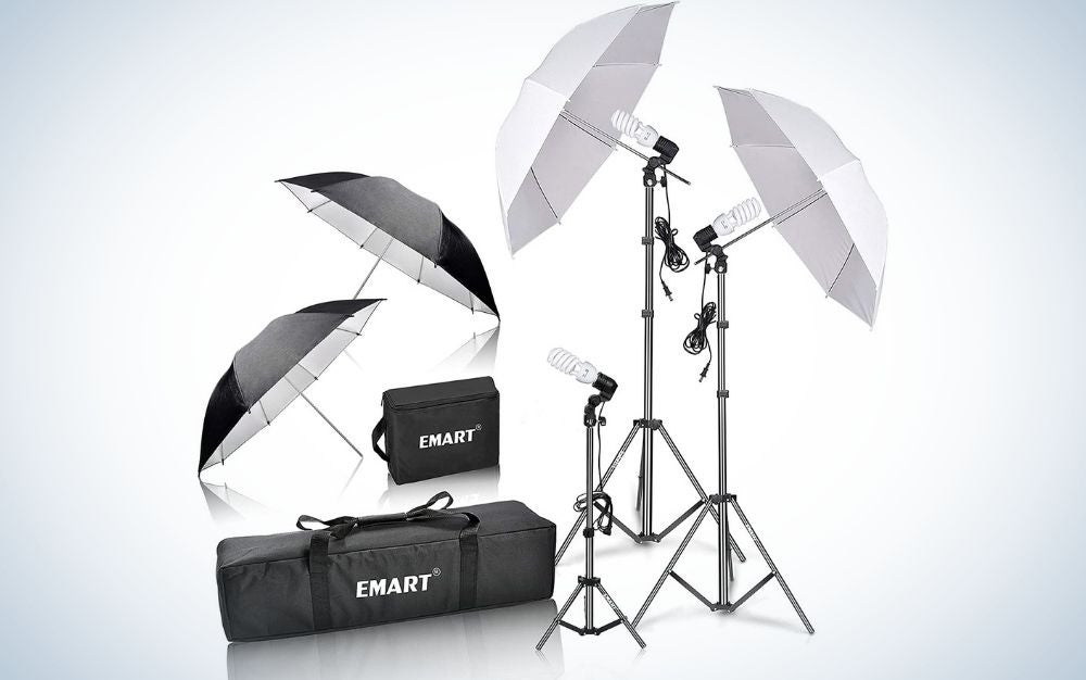 Two open black umbrellas with two thin tails supported by each other, as well as two large white umbrellas with thin and long stick support with black support legs and two black bags, one square and the other in rectangular shape.