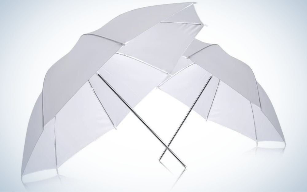 Two open white umbrellas and two thin tails supported by each other.