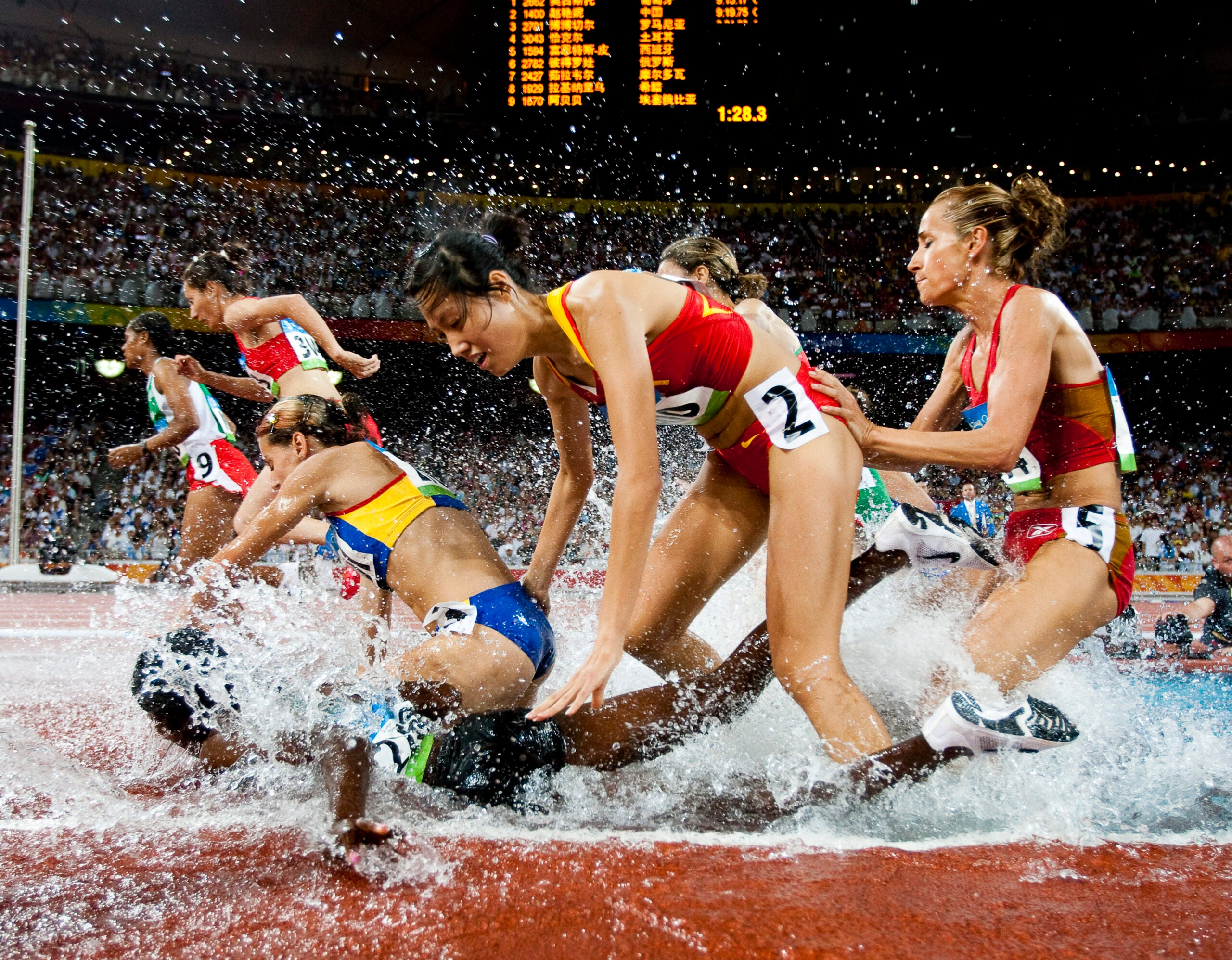 Runners splashing in the steeple chase pit.