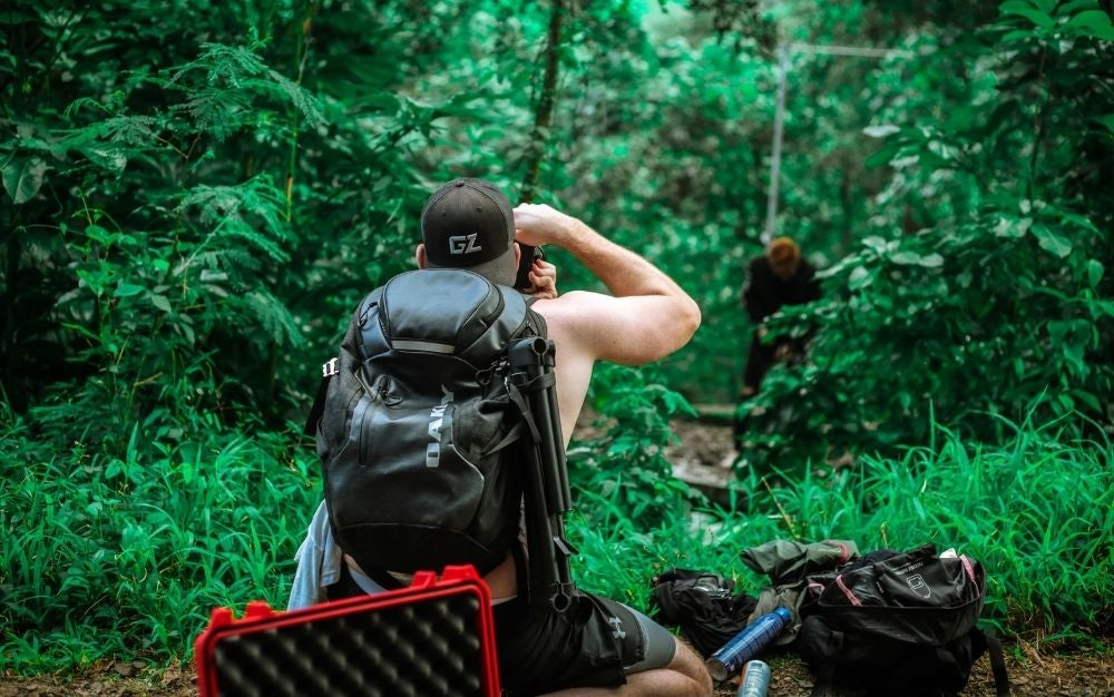 Man carrying a backpack and taking photo in the woods