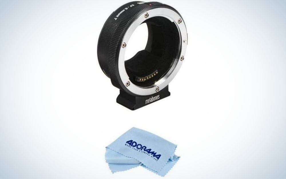 A black lens adapter all with an oval shape and empty space on the inside as well as a blue cloth to clean the lenses.