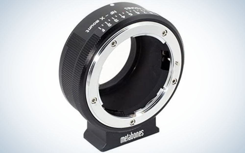 An all-black lens adapter with an oval shape and empty space on the inside as well as a silver arched line around the lens.