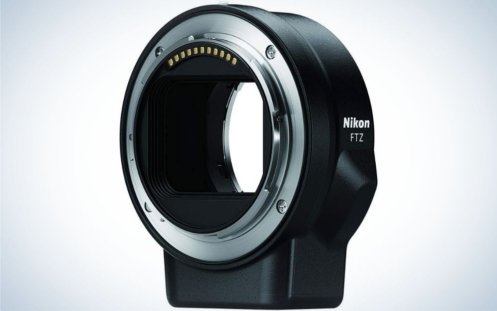 A black Kanon lens adapter all with an oval shape and empty space inside as well as a silver arched line.