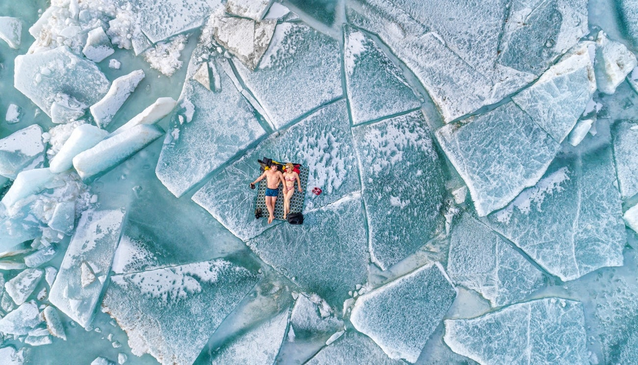 A couple lounges on ice hummocks in the Almaty region of Kazakhstan
